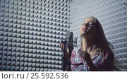 Купить «Attractive woman in recording studio», видеоролик № 25592536, снято 8 февраля 2017 г. (c) Raev Denis / Фотобанк Лори