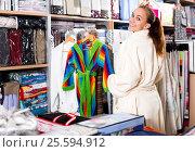 Купить «Girl customer looking for new bathrobe», фото № 25594912, снято 24 февраля 2019 г. (c) Яков Филимонов / Фотобанк Лори
