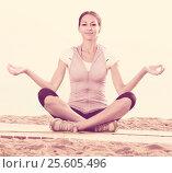 Купить «Smiling woman practise yoga cross-legged», фото № 25605496, снято 22 октября 2018 г. (c) Яков Филимонов / Фотобанк Лори