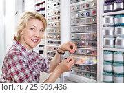 Купить «Female next to shelf with buttons», фото № 25609436, снято 21 апреля 2019 г. (c) Яков Филимонов / Фотобанк Лори