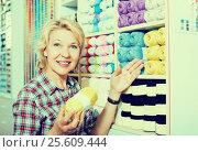 Купить «Woman selecting multicolored yarn», фото № 25609444, снято 20 февраля 2018 г. (c) Яков Филимонов / Фотобанк Лори