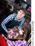 Купить «Grocery worker selling fresh garlic», фото № 25609648, снято 17 февраля 2020 г. (c) Яков Филимонов / Фотобанк Лори