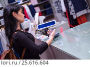 Купить «Mobile payment. Girl pays to shop using mobile phone», фото № 25616604, снято 15 апреля 2014 г. (c) Андрей Армягов / Фотобанк Лори