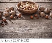 Купить «Mixed nuts on old wooden background», фото № 25619532, снято 21 ноября 2016 г. (c) Майя Крученкова / Фотобанк Лори