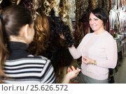 Купить «Two customers purchasing hair extension», фото № 25626572, снято 17 октября 2018 г. (c) Яков Филимонов / Фотобанк Лори