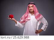 Купить «Arab businessman with piggybank on gray background», фото № 25629988, снято 4 октября 2016 г. (c) Elnur / Фотобанк Лори