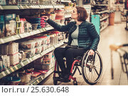 Купить «Disabled woman in a wheelchair in a department store», фото № 25630648, снято 21 октября 2018 г. (c) Andrejs Pidjass / Фотобанк Лори