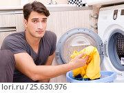 Купить «Young husband man doing laundry at home», фото № 25630976, снято 10 октября 2016 г. (c) Elnur / Фотобанк Лори