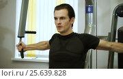 Купить «The young man of athletic build doing fitness training on exercise equipment at gym. HD», видеоролик № 25639828, снято 14 февраля 2017 г. (c) ActionStore / Фотобанк Лори