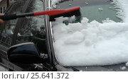 Person scrapes car windshield from snow after blizzard. Стоковое видео, видеограф Igor Vorobyov / Фотобанк Лори