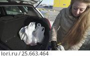 Купить «Young girl puts the plastic bags with purchases from the cart in the trunk of car stock footage video», видеоролик № 25663464, снято 19 февраля 2017 г. (c) Юлия Машкова / Фотобанк Лори