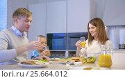 Купить «Young family at dinner», видеоролик № 25664012, снято 19 сентября 2019 г. (c) Raev Denis / Фотобанк Лори