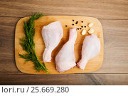 Raw chicken legs on wooden board. Стоковое фото, фотограф Валерия Лузина / Фотобанк Лори