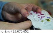 Купить «Close up of girl's hands embroiders a word Mama», видеоролик № 25670652, снято 6 марта 2017 г. (c) Георгий Дзюра / Фотобанк Лори
