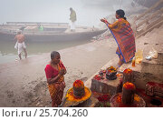 Купить «Pilgrims making a ritual offering and praying, ghats of Ganges river, Varanasi, Uttar Pradesh, India.», фото № 25704260, снято 1 декабря 2016 г. (c) age Fotostock / Фотобанк Лори