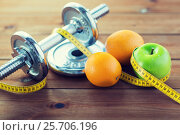 Купить «close up of dumbbell, fruits and measuring tape», фото № 25706196, снято 15 октября 2015 г. (c) Syda Productions / Фотобанк Лори