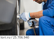 Купить «mechanic with screwdriver changing car tire», фото № 25706940, снято 1 июля 2016 г. (c) Syda Productions / Фотобанк Лори