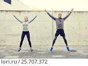 Купить «happy man and woman jumping outdoors», фото № 25707372, снято 17 октября 2015 г. (c) Syda Productions / Фотобанк Лори