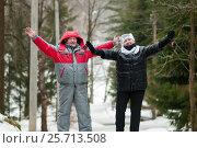 Счастливая семья. Немолодые мужчина и женщина стоят на зимней дороге подняв руки вверх (2017 год). Редакционное фото, фотограф Игорь Низов / Фотобанк Лори