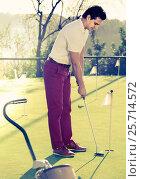 Купить «Man playing golf is going to hit ball at golf course», фото № 25714572, снято 14 ноября 2018 г. (c) Яков Филимонов / Фотобанк Лори
