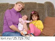 Купить «Молодая женщина с трехлетней дочерью и грудным ребенком сидит на диване», фото № 25729792, снято 12 октября 2014 г. (c) Ирина Борсученко / Фотобанк Лори