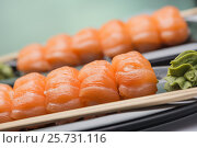 Sushi with a light-salted salmon, wooden sticks and sauce of wasabi on a ceramic dark plate, фото № 25731116, снято 8 марта 2017 г. (c) Anatoly Timofeev / Фотобанк Лори