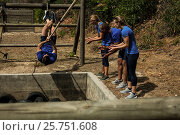 Купить «Man crossing the rope during obstacle course while people cheering him», фото № 25751608, снято 24 ноября 2016 г. (c) Wavebreak Media / Фотобанк Лори