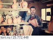 Купить «man potter holding ceramic vessels in atelier», фото № 25772448, снято 20 октября 2018 г. (c) Яков Филимонов / Фотобанк Лори