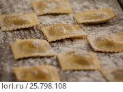 Купить «Ravioli pasta dusted with floor on wooden background», фото № 25798108, снято 13 октября 2016 г. (c) Wavebreak Media / Фотобанк Лори