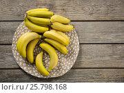 Купить «Overhead of fresh bunch of bananas in plate», фото № 25798168, снято 19 декабря 2016 г. (c) Wavebreak Media / Фотобанк Лори