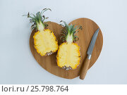 Купить «Overhead of two halved pineapple on chopping board», фото № 25798764, снято 19 декабря 2016 г. (c) Wavebreak Media / Фотобанк Лори