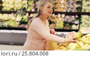 Купить «pregnant woman with bag buying pears at grocery», видеоролик № 25804008, снято 8 февраля 2017 г. (c) Syda Productions / Фотобанк Лори