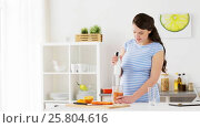 Купить «pregnant woman with blender cooking fruits at home», видеоролик № 25804616, снято 16 марта 2017 г. (c) Syda Productions / Фотобанк Лори