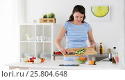 Купить «pregnant woman cooking vegetable salad at home», видеоролик № 25804648, снято 16 марта 2017 г. (c) Syda Productions / Фотобанк Лори