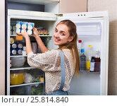 Купить «Positive smiling girl standing near fridge», фото № 25814840, снято 3 апреля 2020 г. (c) Яков Филимонов / Фотобанк Лори