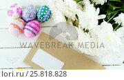 Купить «Multicolored Easter eggs, bunch of flower and envelope on wooden surface», видеоролик № 25818828, снято 9 июля 2020 г. (c) Wavebreak Media / Фотобанк Лори