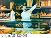 Купить «Male shop assistant demonstrating delicious loaves of bread in bakery», фото № 25820008, снято 26 января 2017 г. (c) Яков Филимонов / Фотобанк Лори