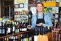 Man seller wearing apron having bottle of wine in hands, фото № 25820168, снято 27 марта 2017 г. (c) Яков Филимонов / Фотобанк Лори