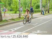 Купить «Девушка с ребенком едет на велосипеде. Парк Сокольники», эксклюзивное фото № 25826840, снято 7 августа 2016 г. (c) Владимир Князев / Фотобанк Лори
