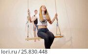 Купить «Happy and attractive young couple relax on swing», видеоролик № 25830448, снято 10 марта 2017 г. (c) Илья Насакин / Фотобанк Лори