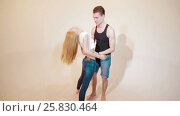 Купить «Happy and attractive young couple dance together», видеоролик № 25830464, снято 10 марта 2017 г. (c) Илья Насакин / Фотобанк Лори