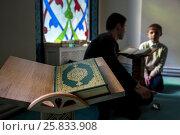Купить «Священная книга мусульман - Коран лежит на подставке в молельном зале Московской соборной мечети, Россия», фото № 25833908, снято 26 марта 2017 г. (c) Николай Винокуров / Фотобанк Лори