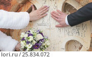 Newlyweds put hands with rings to wall of church. Стоковое видео, видеограф worker / Фотобанк Лори