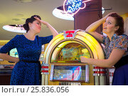 Купить «Two girls dream about a musical machine in bar», фото № 25836056, снято 18 января 2015 г. (c) Losevsky Pavel / Фотобанк Лори