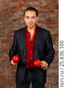 Купить «Young man in suit stands with red maracas in studio with brick wall», фото № 25836100, снято 9 февраля 2016 г. (c) Losevsky Pavel / Фотобанк Лори