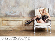 Купить «Beautiful girl in a sexy black lingerie and high-heel shoes sits on armchair in empty room», фото № 25836112, снято 17 сентября 2015 г. (c) Losevsky Pavel / Фотобанк Лори