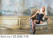 Купить «Young blonde woman in black lingerie and high-heel shoes sits in armchair in empty room», фото № 25836116, снято 17 сентября 2015 г. (c) Losevsky Pavel / Фотобанк Лори
