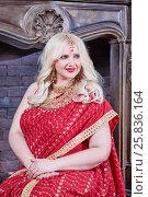 Купить «Smiling blonde woman in red dress sits at fireplace in room», фото № 25836164, снято 17 сентября 2015 г. (c) Losevsky Pavel / Фотобанк Лори