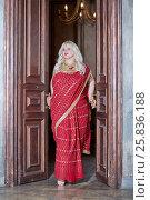 Купить «Blonde woman in red dress stands in doorway, holding doors handles», фото № 25836188, снято 17 сентября 2015 г. (c) Losevsky Pavel / Фотобанк Лори