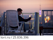 Young man adjusts hookah cap sitting in armchair on highrise roof at sunset dusk. Стоковое фото, фотограф Losevsky Pavel / Фотобанк Лори